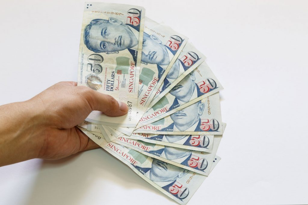 Man holding many fifty dollar notes in hand after getting a 12 month loan cash loan approved