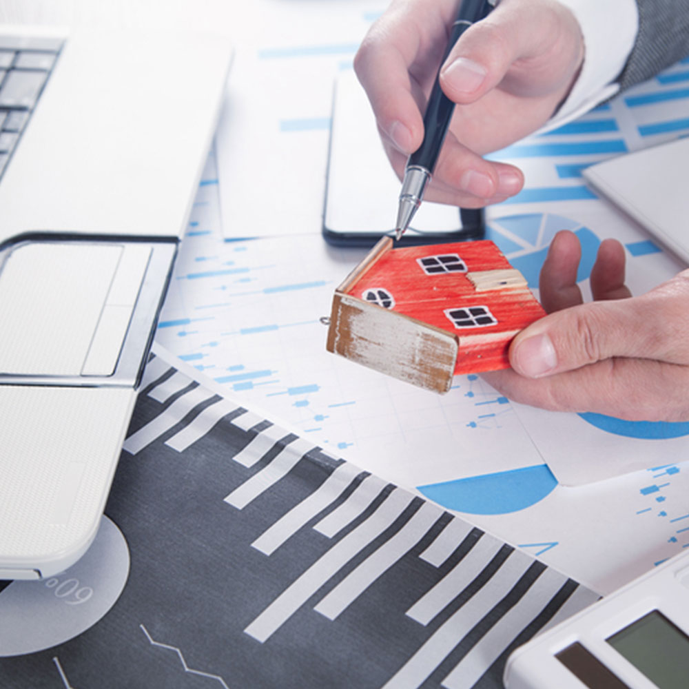 Man holding house model and calculating the process of bridging loan