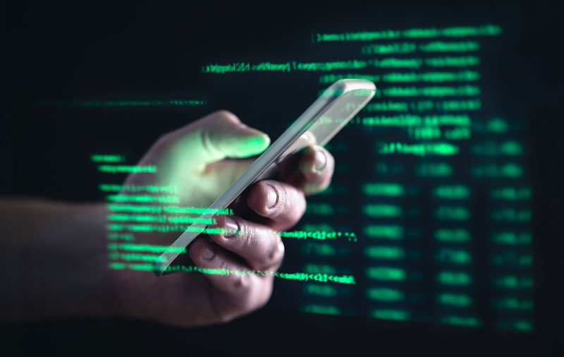 Hacker holding mobile phone emphasising the rising loan scams in Singapore